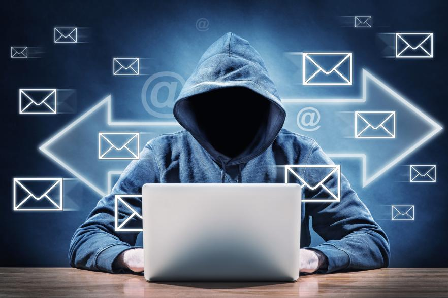 hacker with laptop and mail icons surrounding him